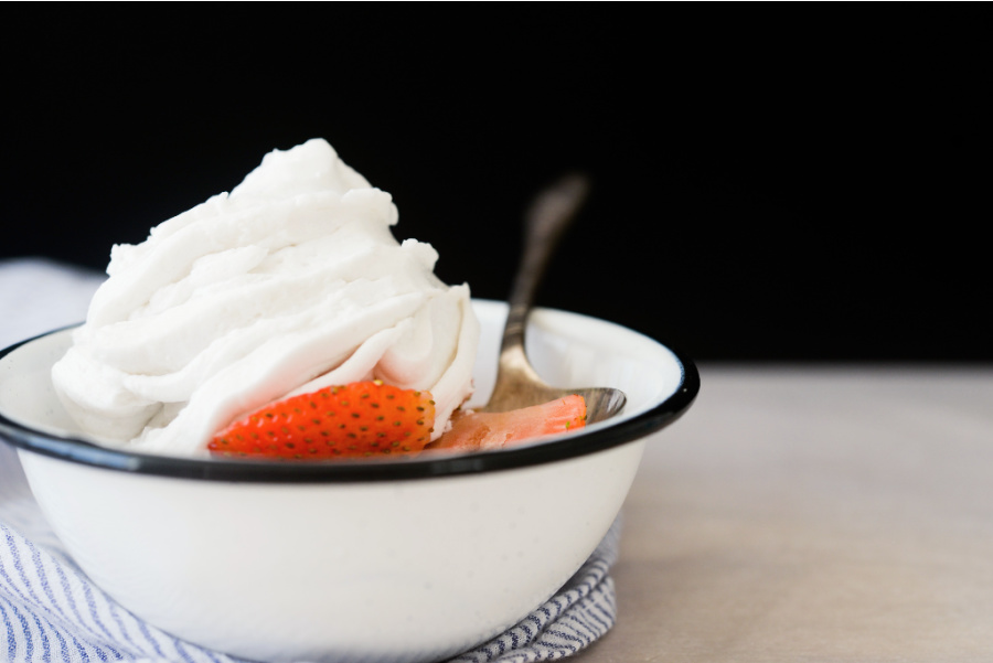 white bowl with strawberries and coconut whipped cream