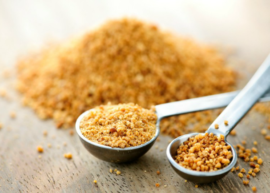 two metal tablespoons of coconut sugar on a grey table