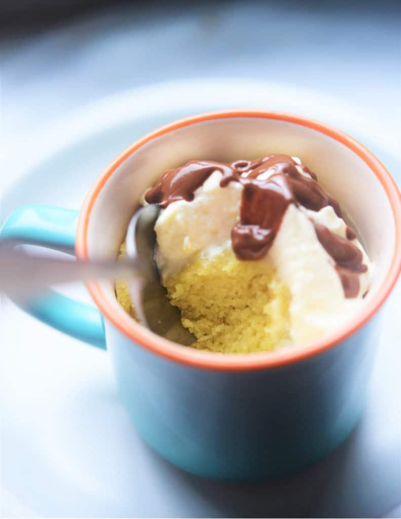 mug filled with keto cake and whipped cream and chocolate sauce