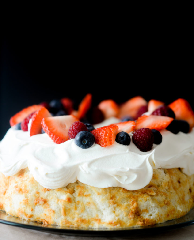 coconut flour angel food cake with whipped cream and berries