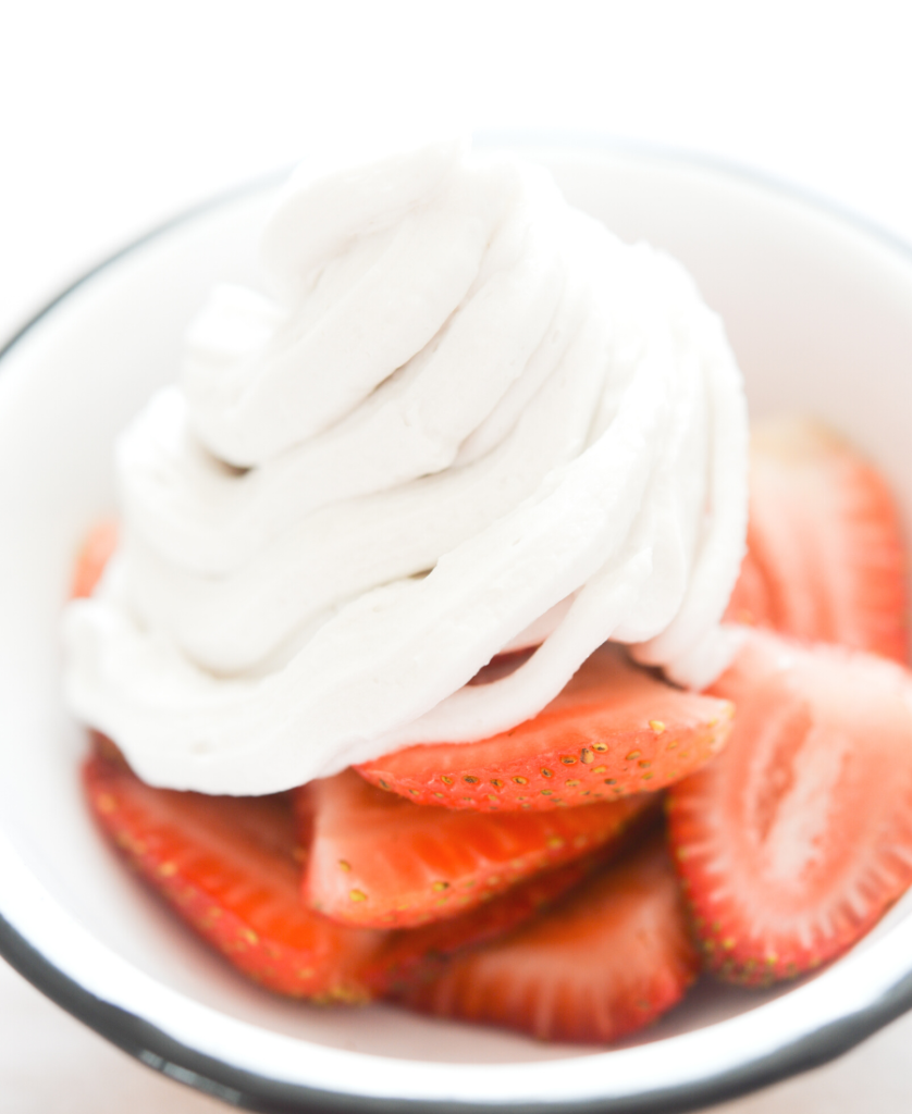 bowl of strawberries topped with coconut whipped cream