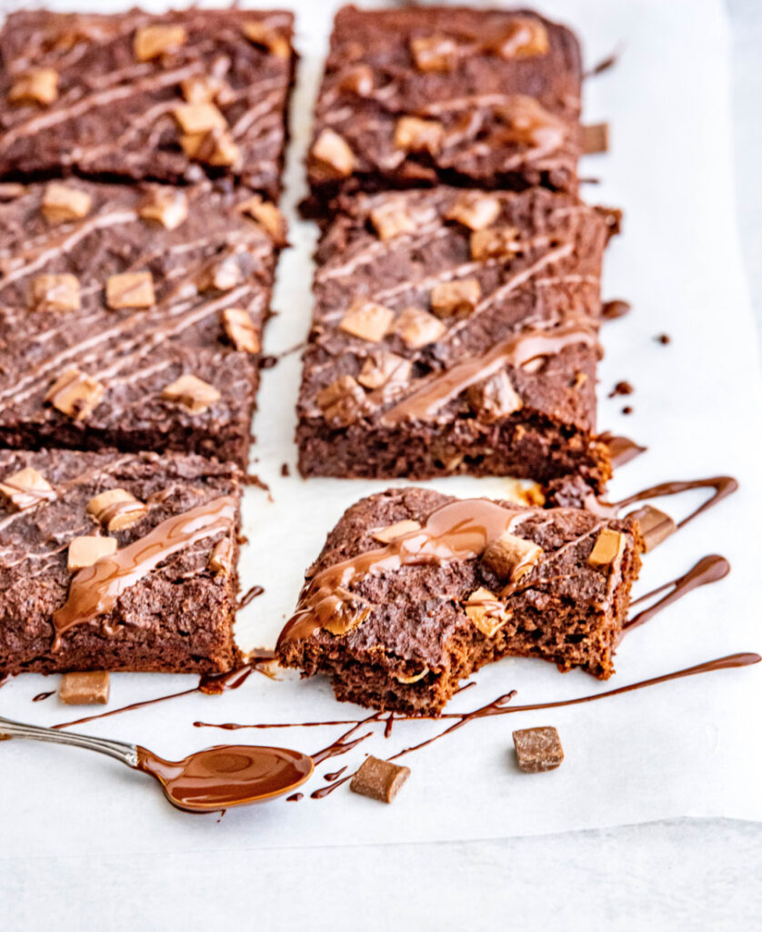 coconut flour brownies topped with a coconut chocolate drizzle