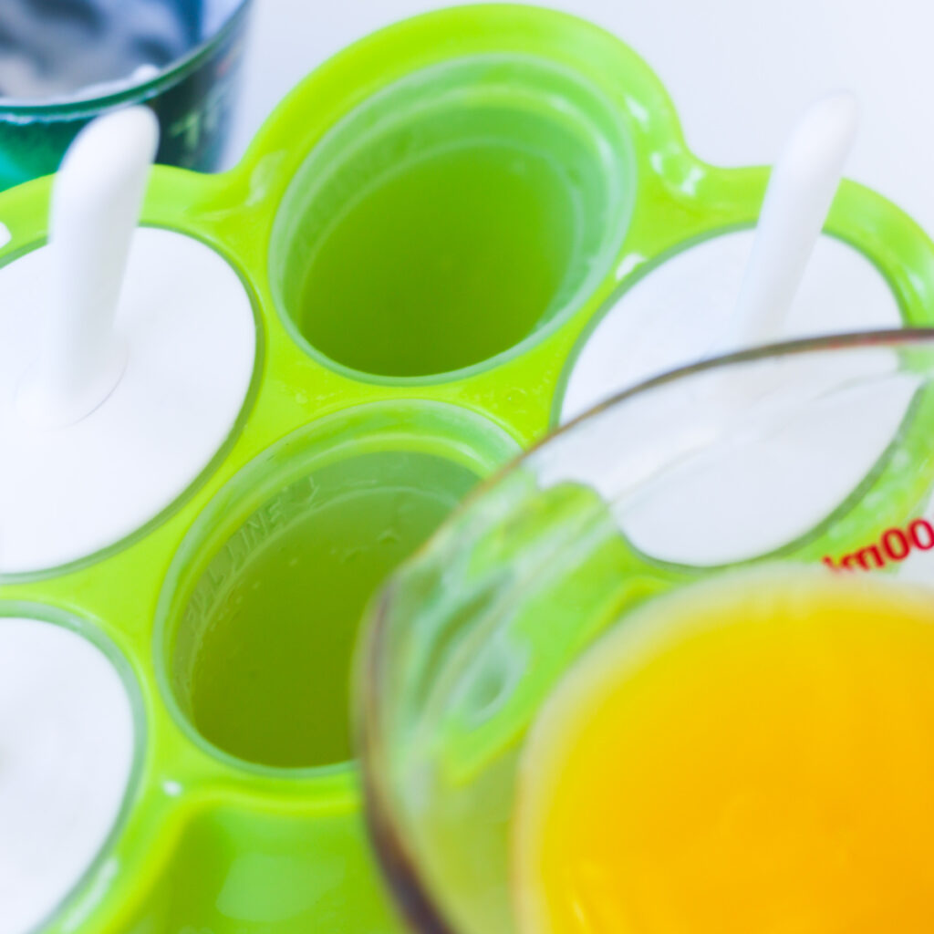 Pouring orange juice into popsicle molds
