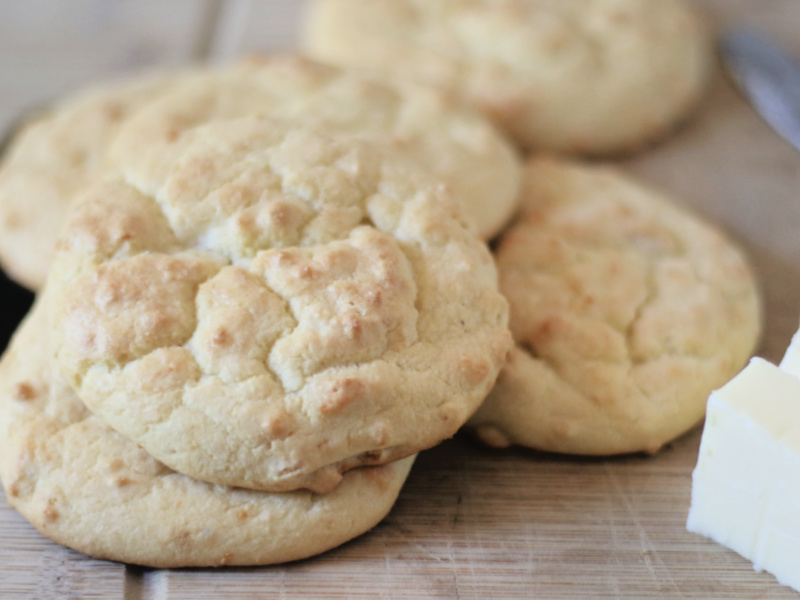 coconut flour biscuits on a cutting board with butter