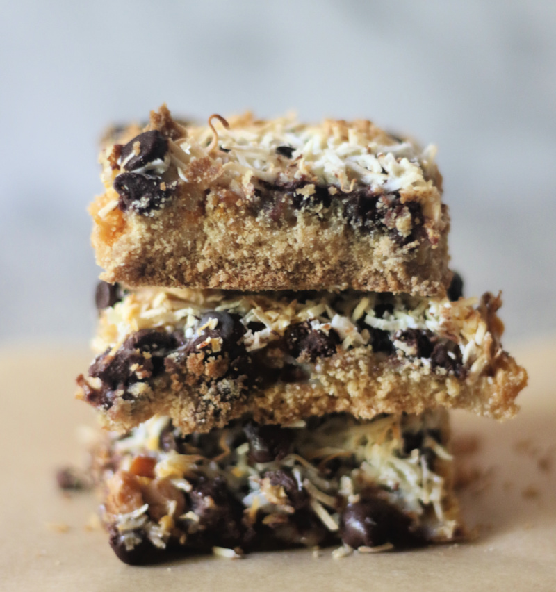 Paleo Magic Cookie Bars, stacked on parchment paper